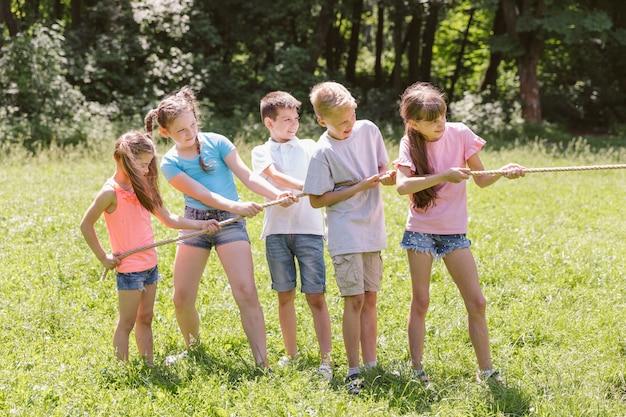 Meninas e meninos jogando cabo de guerra