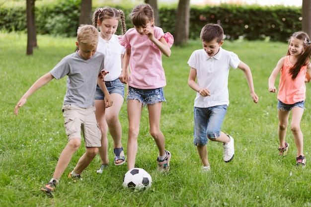 Meninas e meninos jogando futebol