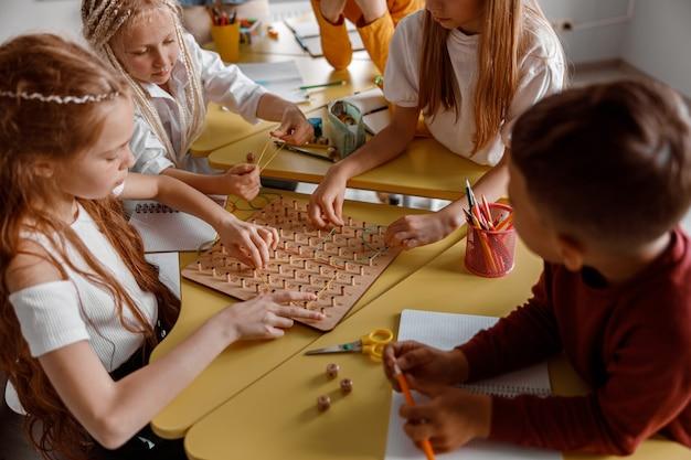 Meninas e meninos treinando habilidades analíticas e criativas