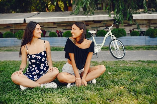 Meninas elegantes andando em um parque de verão