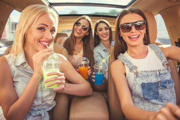 Meninas elegantes bebendo cocktails em um carro