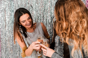 Meninas elegantes brindando com champanhe