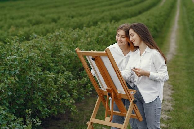 Meninas elegantes e bonitas, pintando em um campo