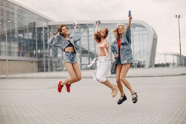 Meninas elegantes e elegantes em pé perto do aeroporto