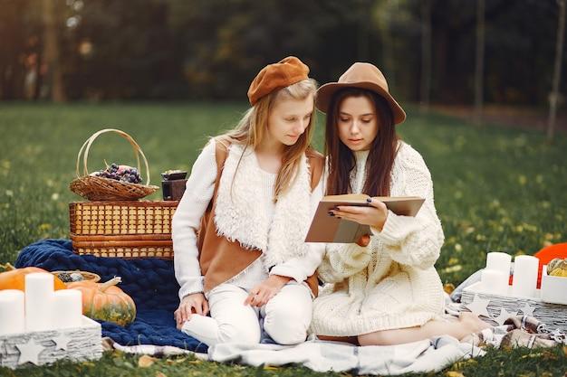 Meninas elegantes e elegantes, sentado em um parque de outono