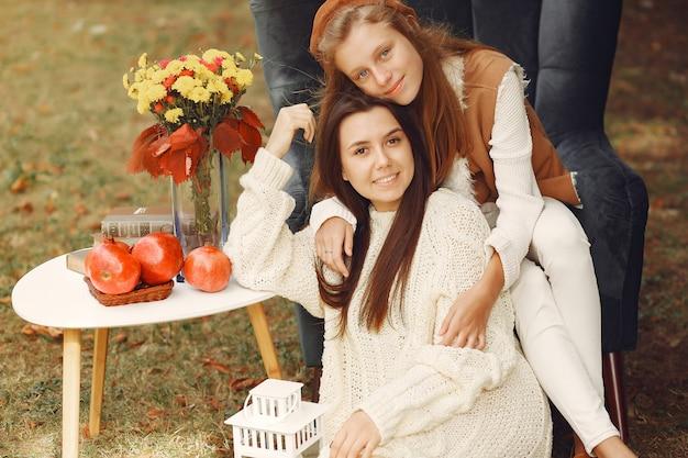 Meninas elegantes e elegantes, sentado em uma cadeira em um parque
