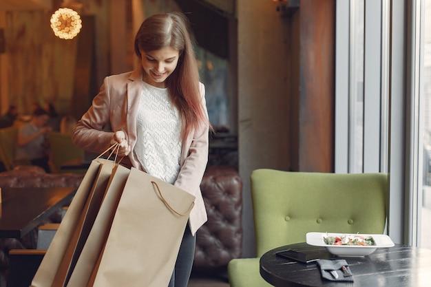 Meninas elegantes em pé em um café com sacolas de compras