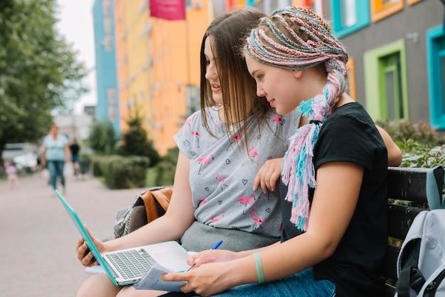 Meninas elegantes que estudam com laptop na rua
