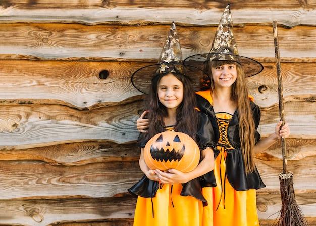 Meninas, em, bruxas, trajes, abraçando, sorrindo, segurando, broomstick, e, abóbora