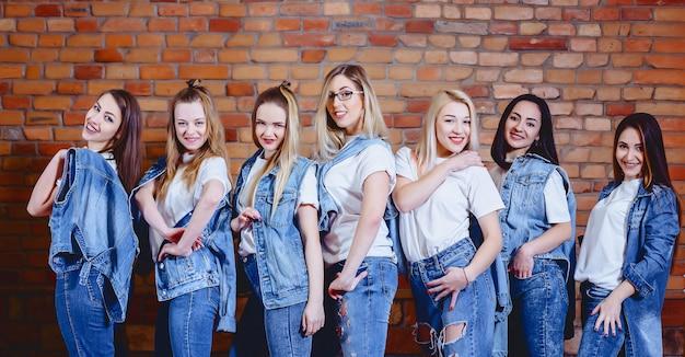 Meninas, em, calças brim, em, fundo, de, parede tijolo