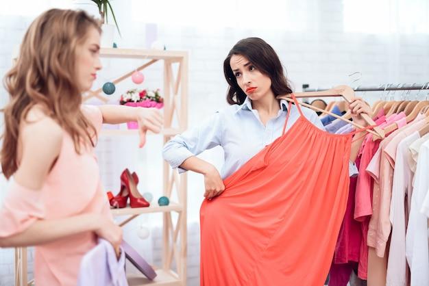 Meninas em compras. as meninas escolhem roupas na loja.