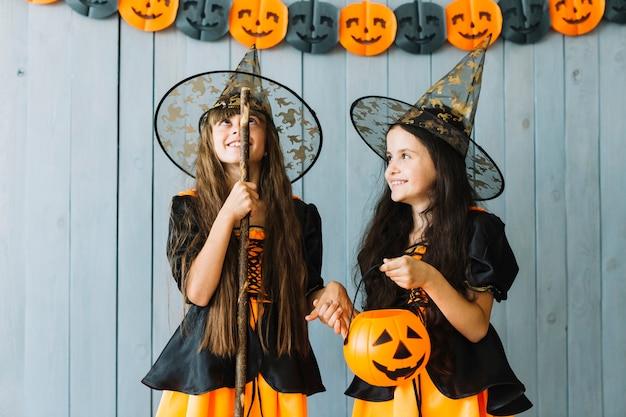 Meninas, em, dia das bruxas, trajes, segurando mão, sorrindo