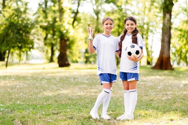 Meninas em equipamento de futebol posando com espaço de cópia