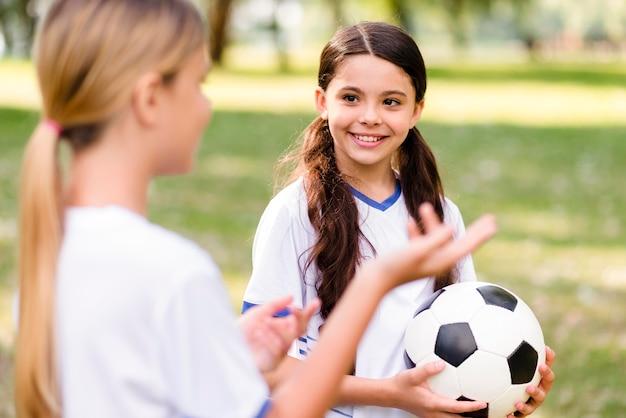 Meninas em equipamentos de futebol falando sobre a partida