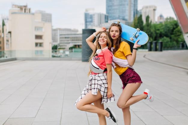 Meninas em êxtase em pé sobre uma perna só e sorrindo, aproveitando o fim de semana e o bom tempo