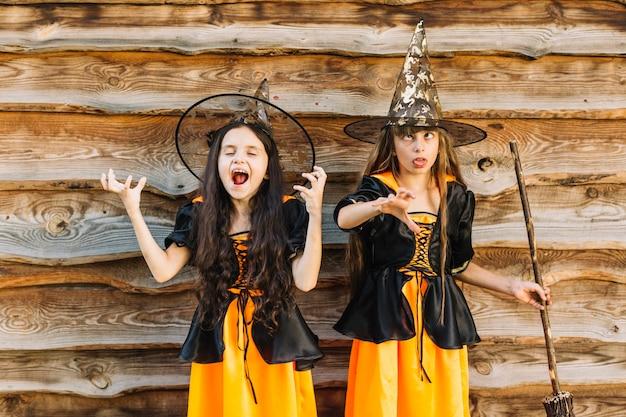 Meninas em fantasias de bruxa posando e fazendo caretas em fundo de madeira