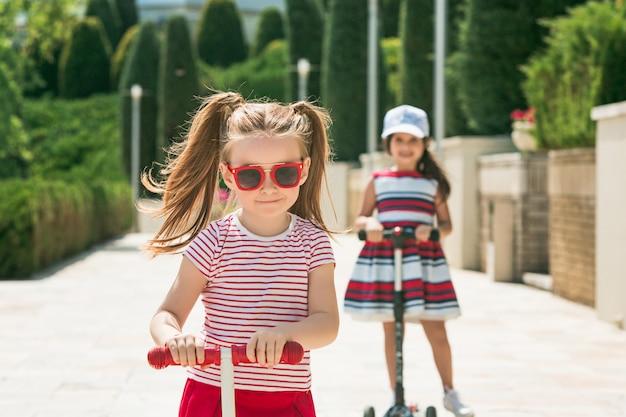 Meninas em idade pré-escolar andando de scooter ao ar livre.