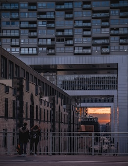 Meninas em pé perto da grade assistindo ao pôr do sol