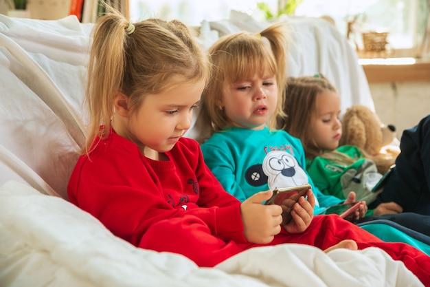 Meninas em pijamas quentes e macios brincando em casa