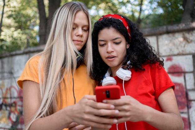 Meninas em tiro médio olhando para o telefone
