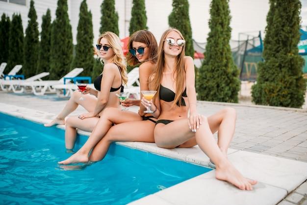 Meninas em trajes de banho, tomando banho de sol à beira da piscina