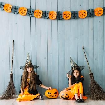 Meninas em trajes de bruxa e chapéus pontudos sentado por cerca