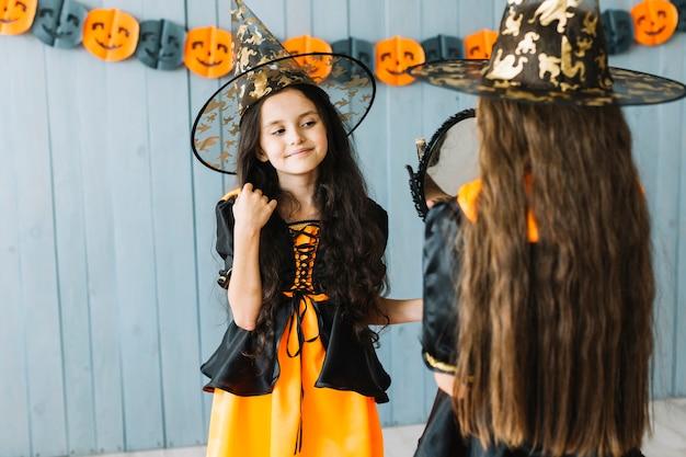 Meninas em trajes de bruxa em pé em frente