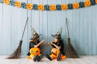 Meninas em trajes de bruxa fazendo gestos assustadores