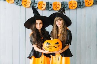Meninas em trajes de bruxa segurando abóbora juntos