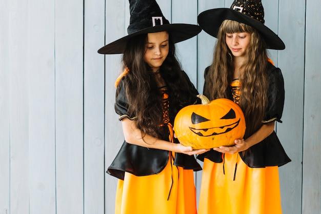 Meninas em trajes de bruxa segurando e olhando para a abóbora
