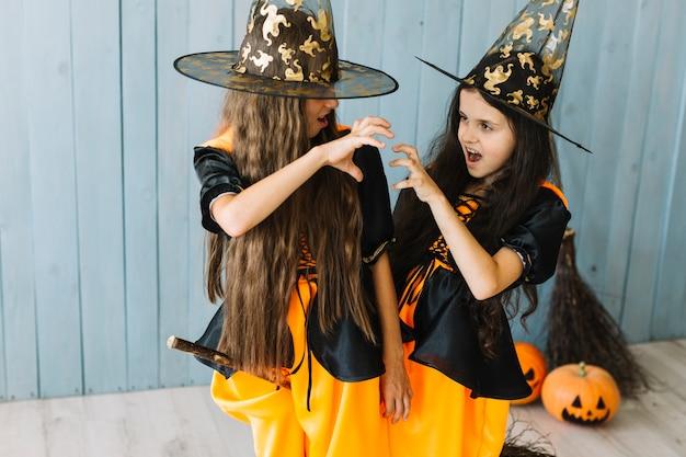Meninas em trajes de bruxa sentado na vassoura fazendo gestos assustadores