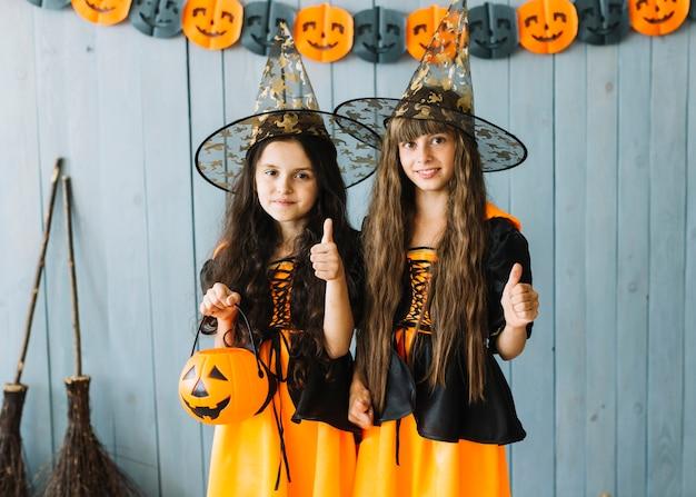 Meninas em trajes de bruxa sorrindo com polegares para cima