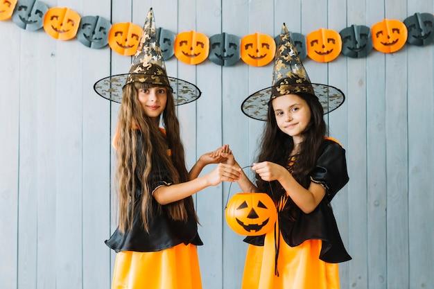 Meninas em trajes de halloween segurando balde de abóbora