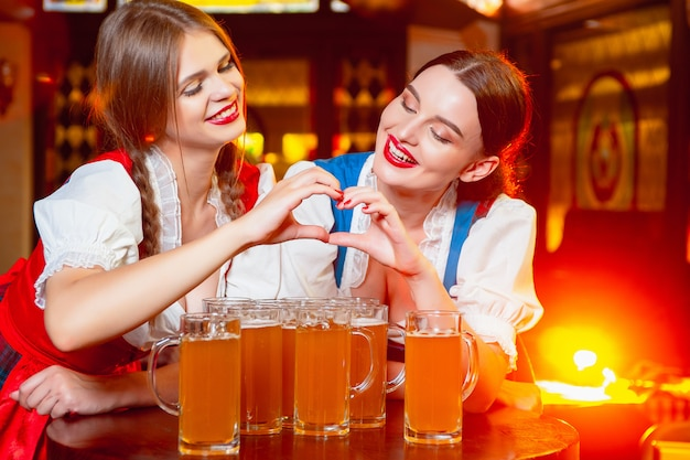 Meninas em trajes nacionais fizeram um coração com as mãos sobre copos de cerveja no festival da oktoberfest.