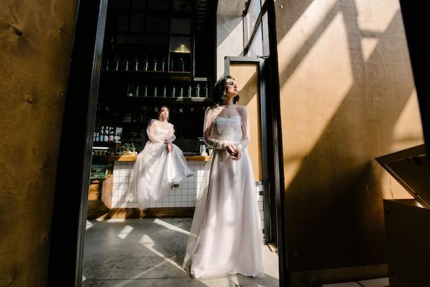 Meninas em vestidos de noiva branco estão posando.
