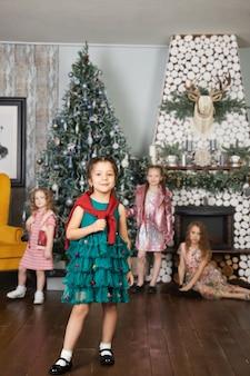 Meninas em vestidos elegantes perto da árvore de natal