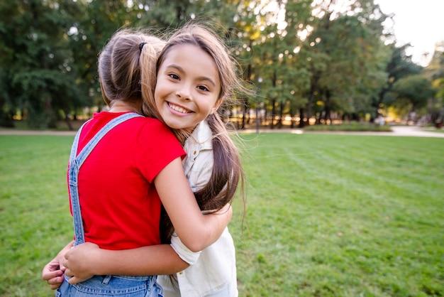 Meninas encantadoras, abraçando-se ao ar livre