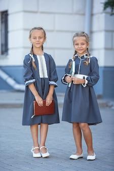Meninas encantadoras com vestido retrô, andando pela cidade em um dia ensolarado de verão.