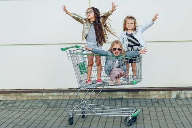 Meninas engraçadas alegres no carrinho de compras