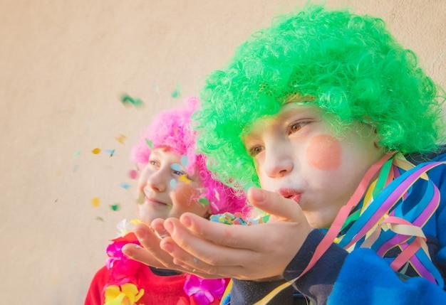 Meninas engraçadas crianças comemoram carnaval sorrindo e se divertindo com confetes coloridos