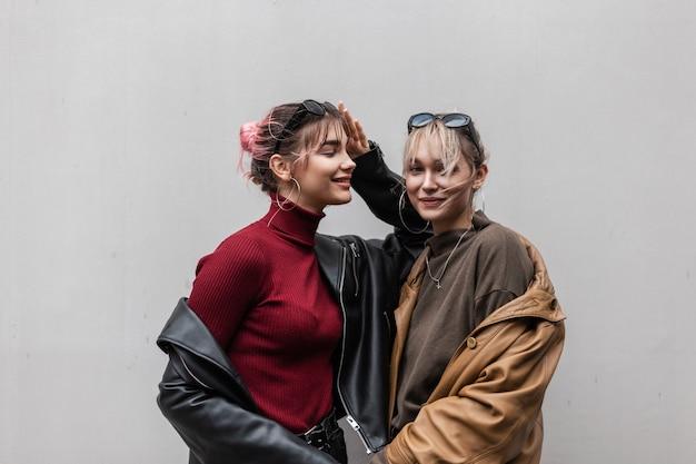 Meninas engraçadas e lindas irmãs em roupas da moda com uma jaqueta de couro e um suéter de tricô ficam perto de uma parede cinza ao ar livre