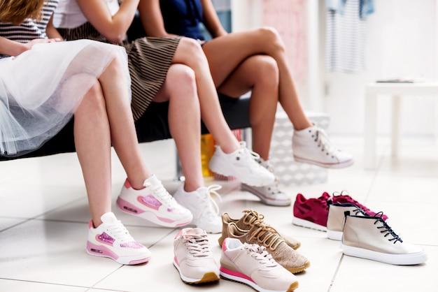 Meninas, escolhendo sapatos, cercados por calçados na loja de roupas da moda