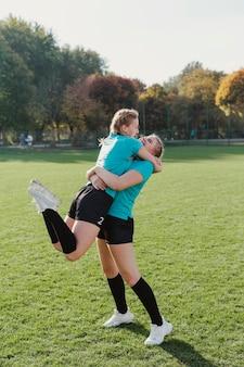 Meninas esportivas felizes, abraçando uns aos outros