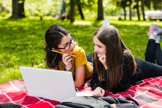 Meninas estudando e debruçando no parque Foto gratuita