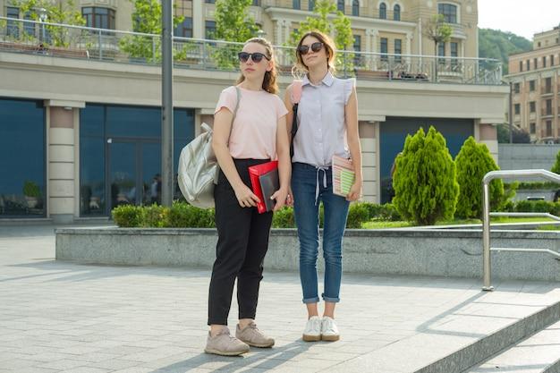 Meninas estudantes com mochilas, livros vão para a escola