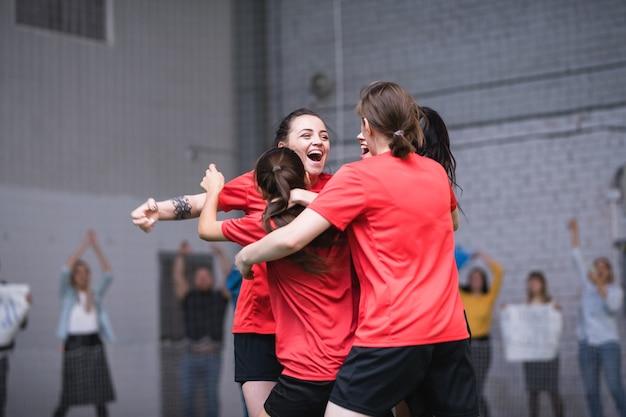 Meninas extasiadas em uniformes esportivos se abraçando após um gol bem sucedido durante um jogo no campo de futebol