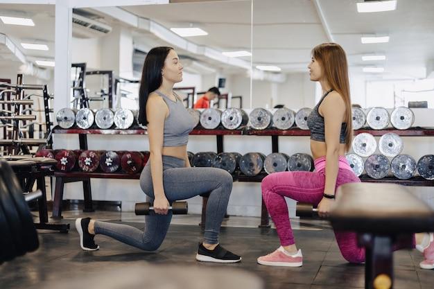 Meninas fazem halteres no ginásio, fitness