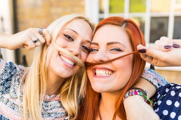 Meninas fazendo bigodes com cabelo