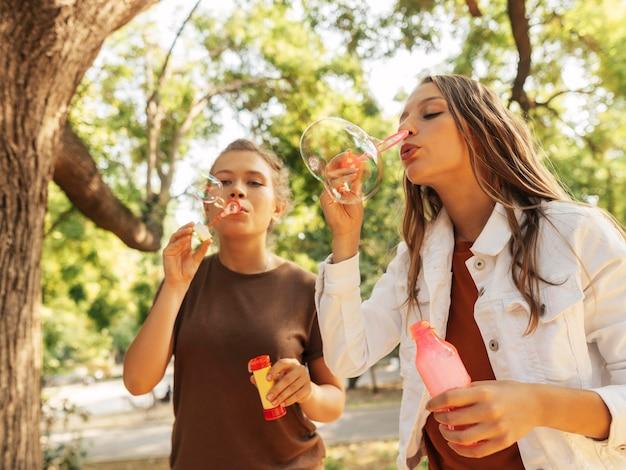 Meninas fazendo bolhas de sabão