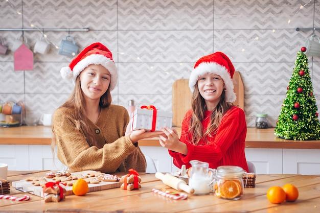 Meninas fazendo casa de pão de mel de natal na lareira na sala decorada.